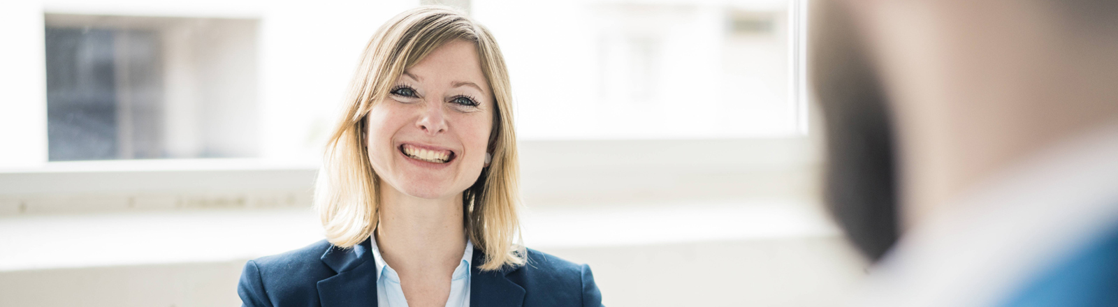 Frau beim Bewerbungsgespräch lächelt sehr selbstbewusst
