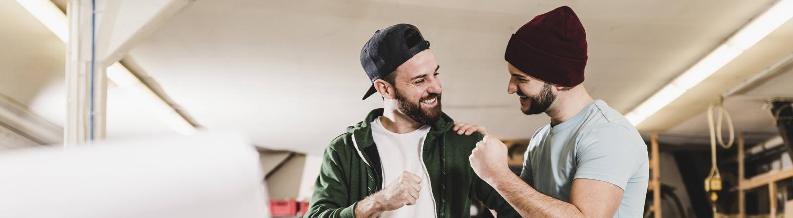 Zwei Typen: Einer legt dem anderen eine Hand auf die Schulter.