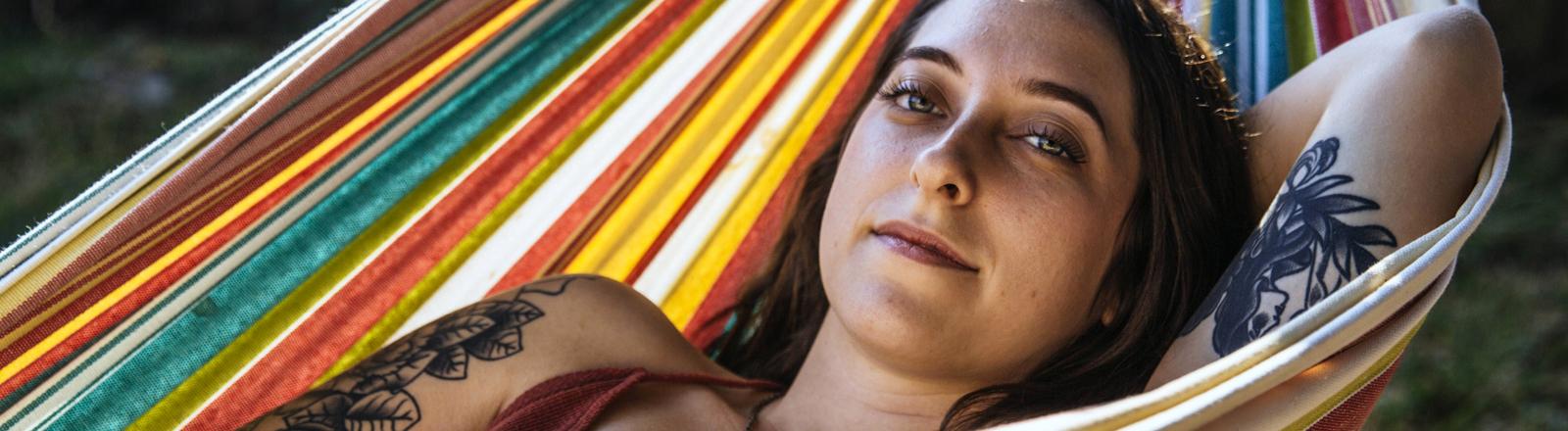 Frau liegt in einer Hängematte und entspannt sich.