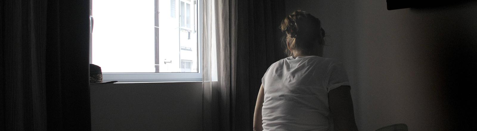 Frau sitzt in einem dunklen Zimmer auf dem bett mit dem Rücken zum Fotografen.
