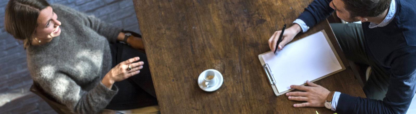 Gespräch mit dem Psychotherapeuten an einem Holztisch.