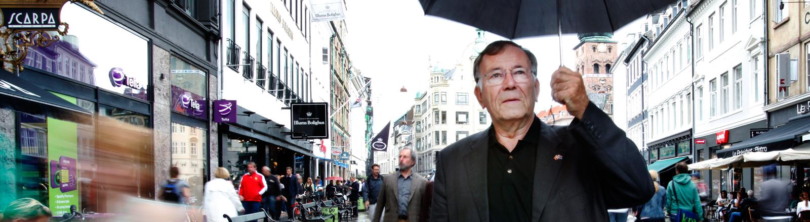 Jan Gehl steht mit einem Regenschirm in einer Fußgängerzone