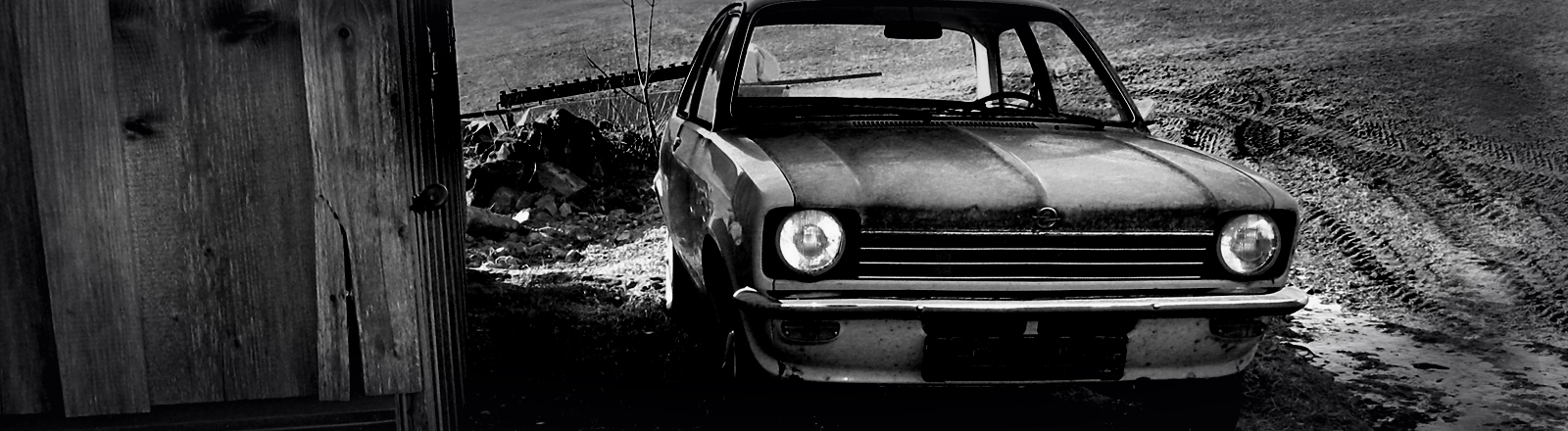 Ein alter Opel Kadett  steht neben einem Holzschuppen