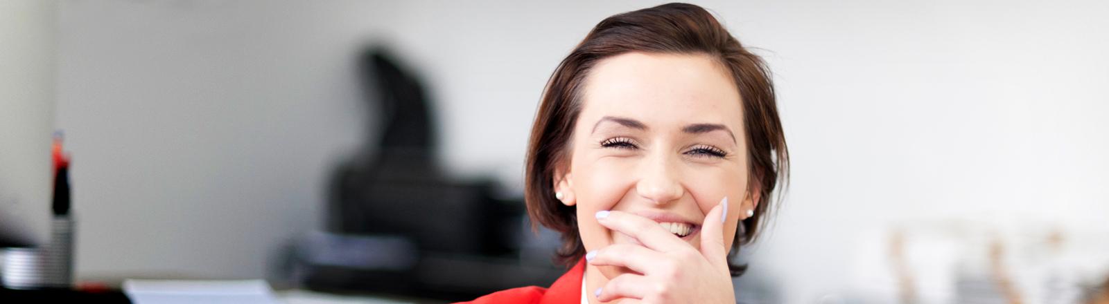 Eine Frau im Businessoutfit lacht