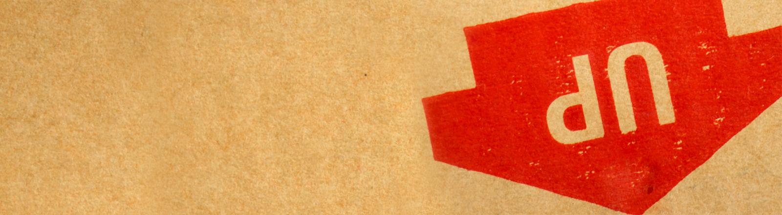 Das Up-Zeichen auf einem Umzugskarton zeigt nach unten.