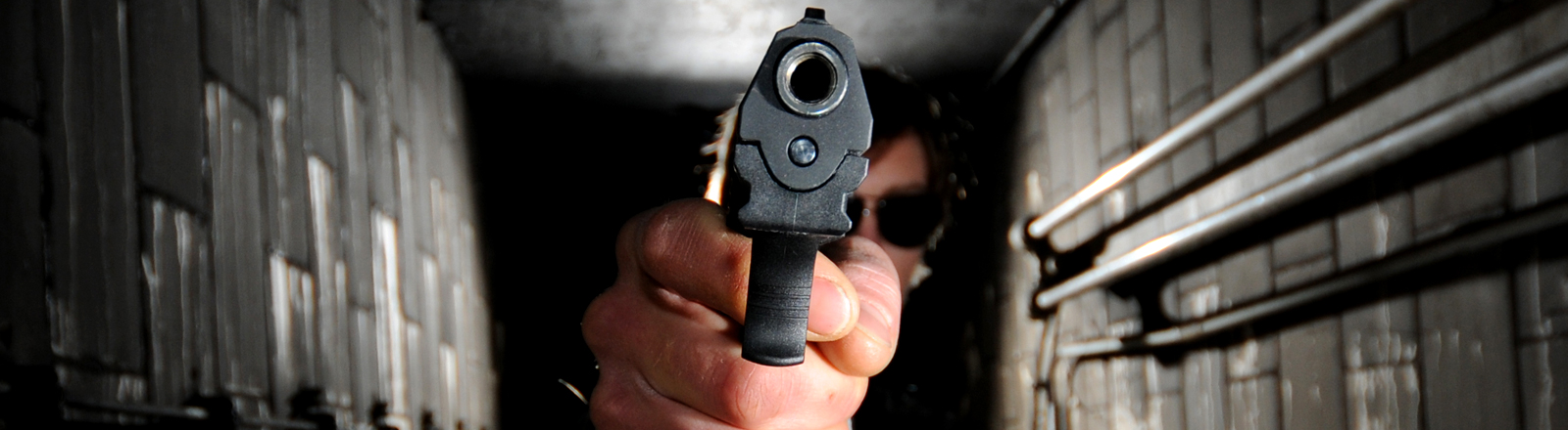 Ein Mann mit Sonnenbrille zielt in einem schmalen Kellergang mit einer Waffe auf die Kameralinse