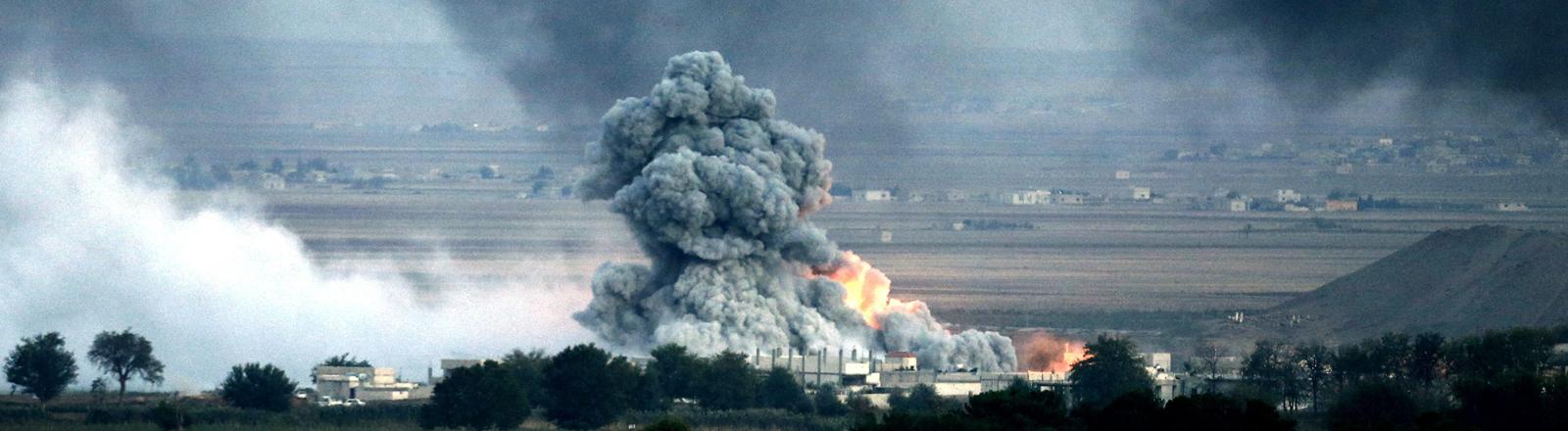 In der Stadt Kobane steht bei Kämpfen zwischen Kurden und IS ein Gebäude in Flammen