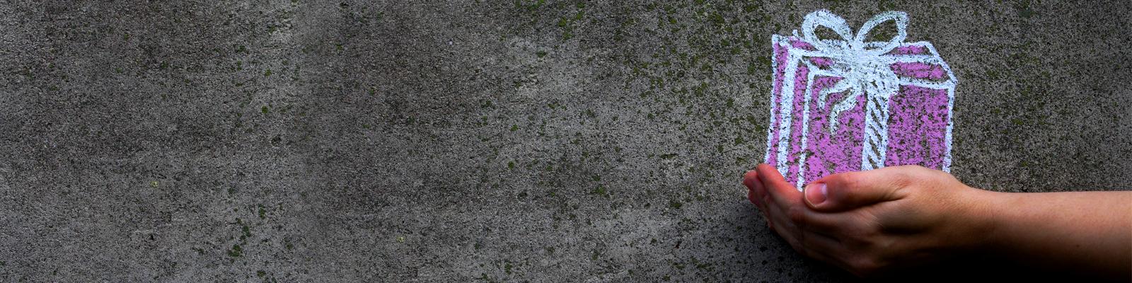 Eine Hand vor einer Wand, darauf ist mit Kreide ein Geschenkpäckchen gemalt