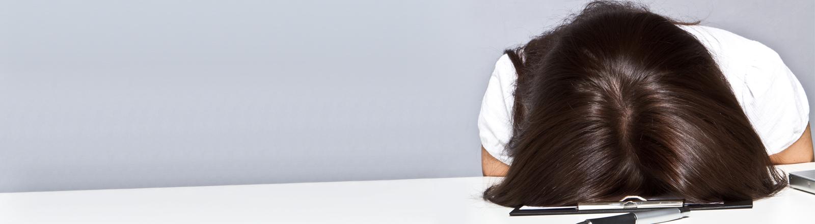Eine Frau hat den Kopf auf dem Tisch, auf einem Klemmbrett