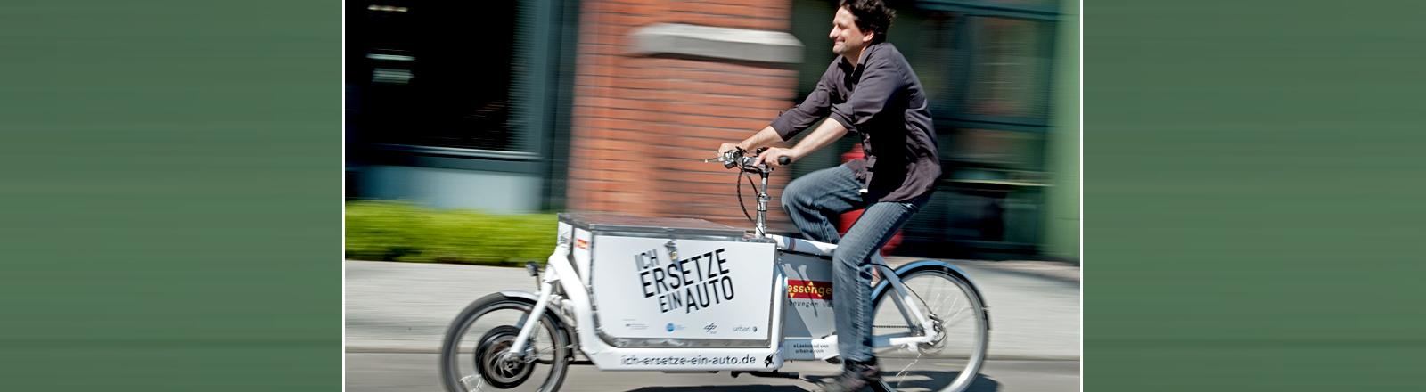 Mann mit einem E-Bike, das vorne einen Laderaum hat.