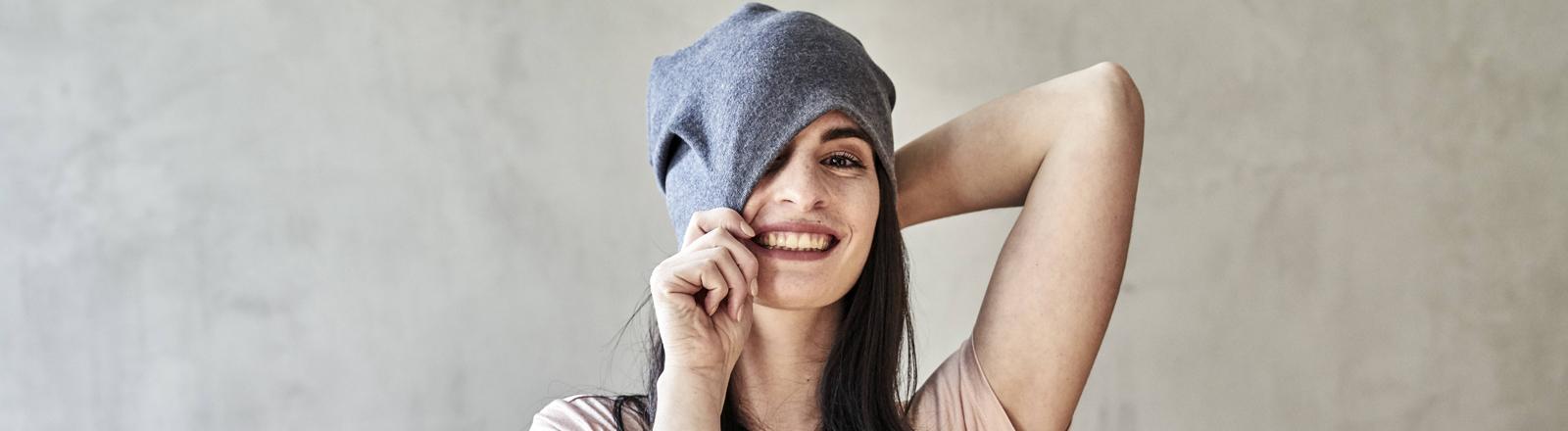 Eine junge Frau lächelt und zieht sich eine Mütze über den Kopf