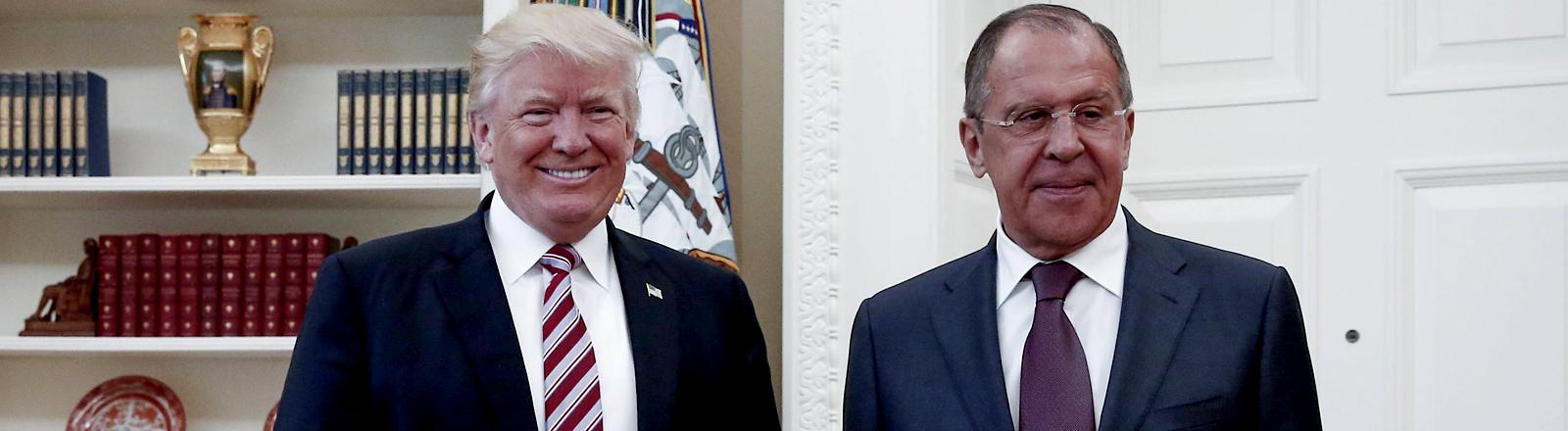 Zwei Männer - Trump und Lawrow - lächeln in die Kameras.