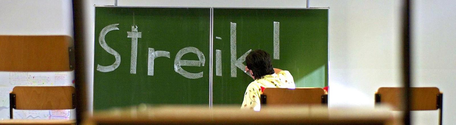 eine Lehrerin schreibt das Wort Streik mit Kreide an eine Tafel
