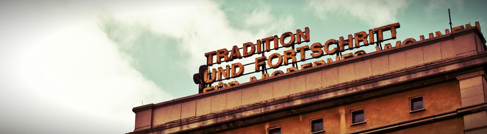 Auf einem Haus steht der Schriftzug Tradition und Fortschritt