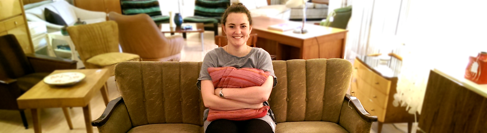 Lena Breuer sitzt in einem Retromöbelladen auf einem alten Sofa.