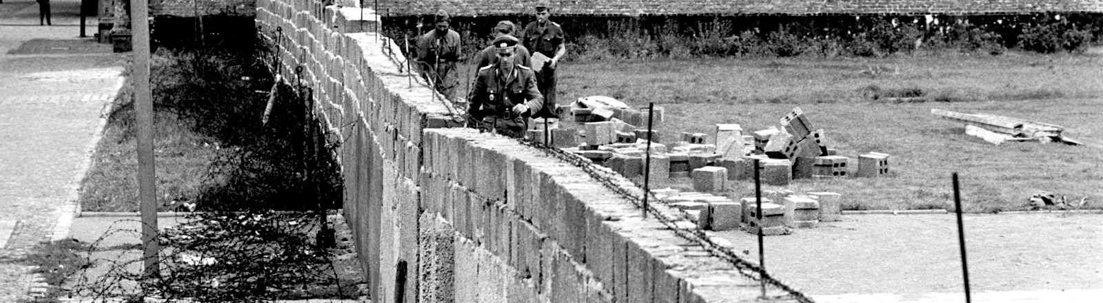An einer Straße wird entlang eines Bürgersteigs eine Mauer gebaut, davor liegen Rollen von Stacheldraht