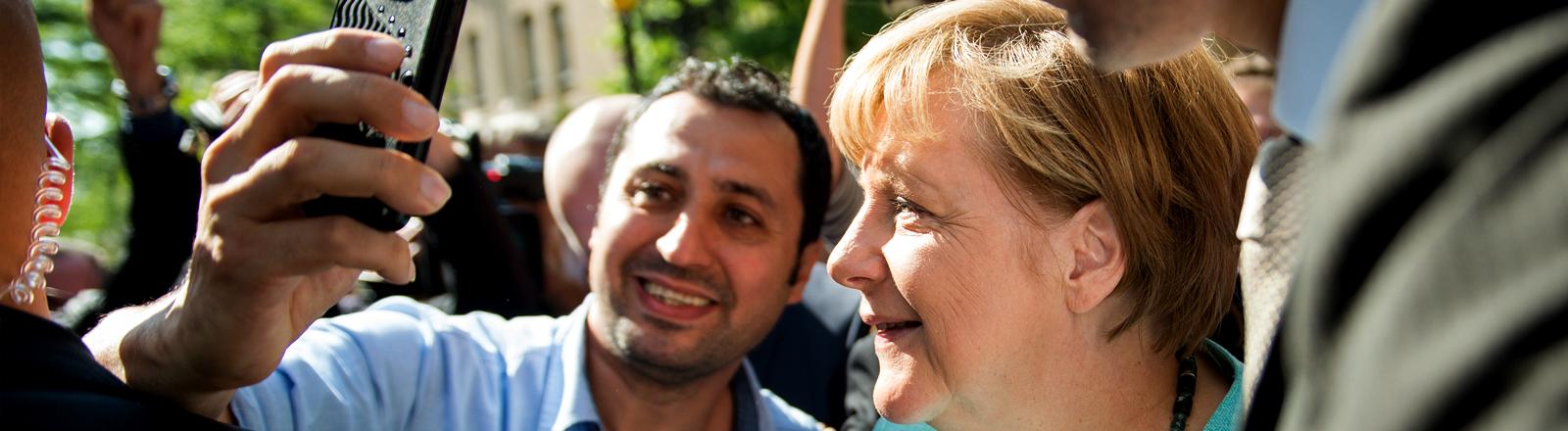 Angela Merkel macht bei ihrem Besuch in einem Flüchtlingsunterkunft in Berlin Selfies mit den Bewohnern