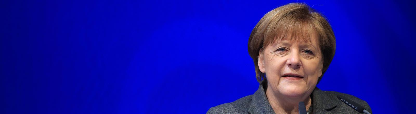 Angela Merkel spricht vor einer blauen Wand