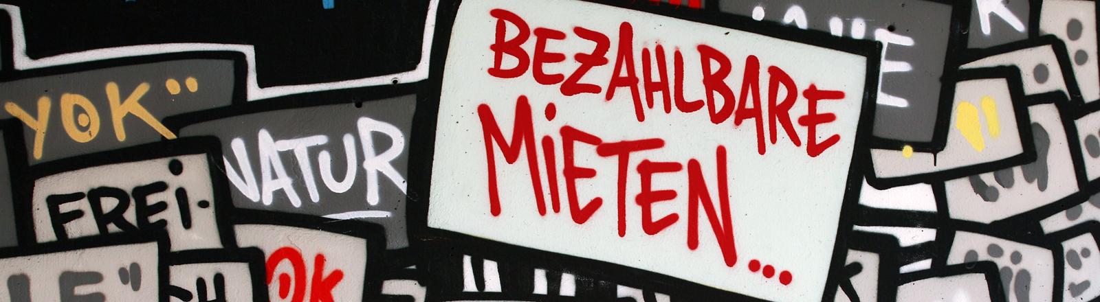 """""""Bezahlbare Miete"""" steht als Graffiti auf einer Wand."""