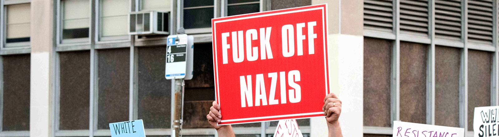 """Mann hält ein Schild hoch, auf dem """"Fuck off Nazis"""" steht."""