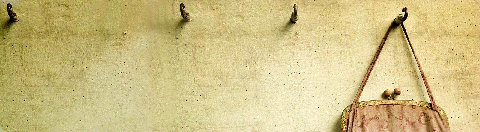 Eine alte Stofftasche hängt an einer Wand