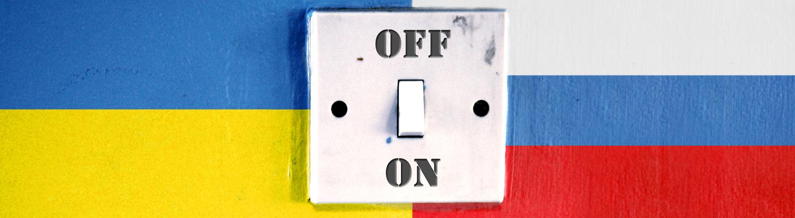Auf eine Wand sind die Flaggen von Ukraine und Russland gemalt, auf der Wand ist ein Lichtschalter in Off-Stellung