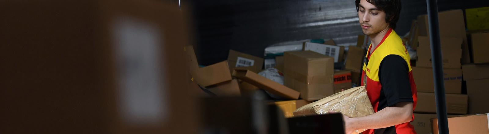 Paketbote beim Sortieren von Paketen