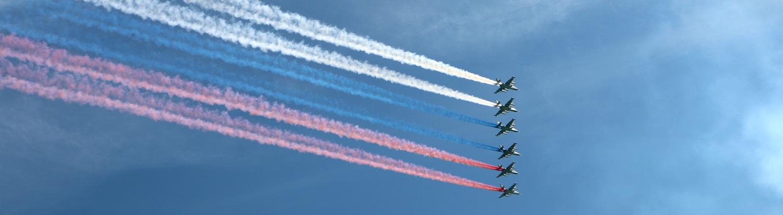 Sechs Flugzeuge in präzisem Abstand malen mit buntem Rauch die russische Flagge in die Luft