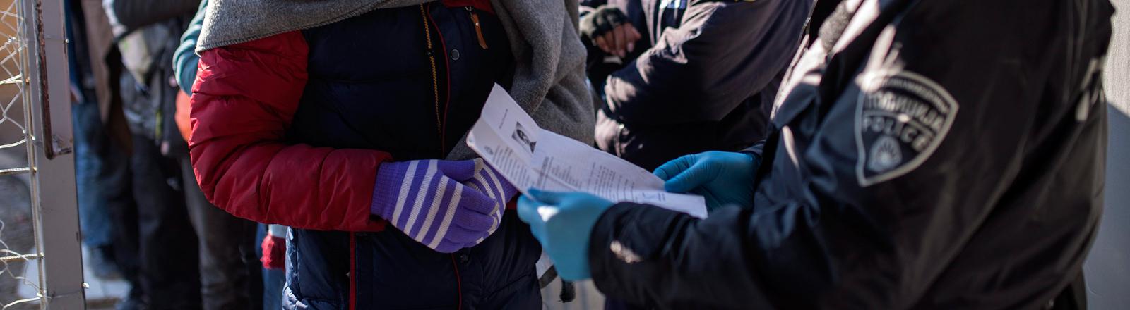 Ein Polizist kontrolliert an der mazedonischen Grenze die Papiere eines Flüchtlings