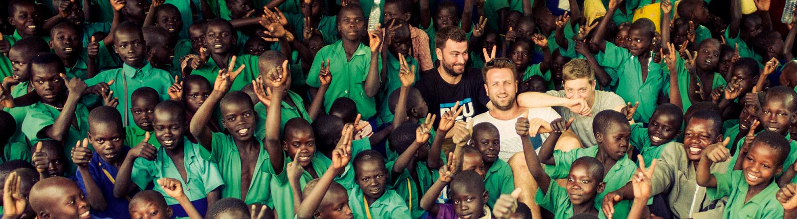 Paul Ripke und Marteria inmitten einer Horde Kinder in Uganda