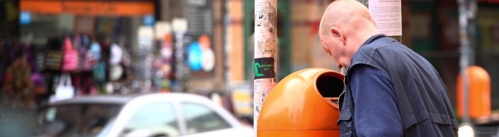 Ein Mann schaut in einen orangenen Mülleimer