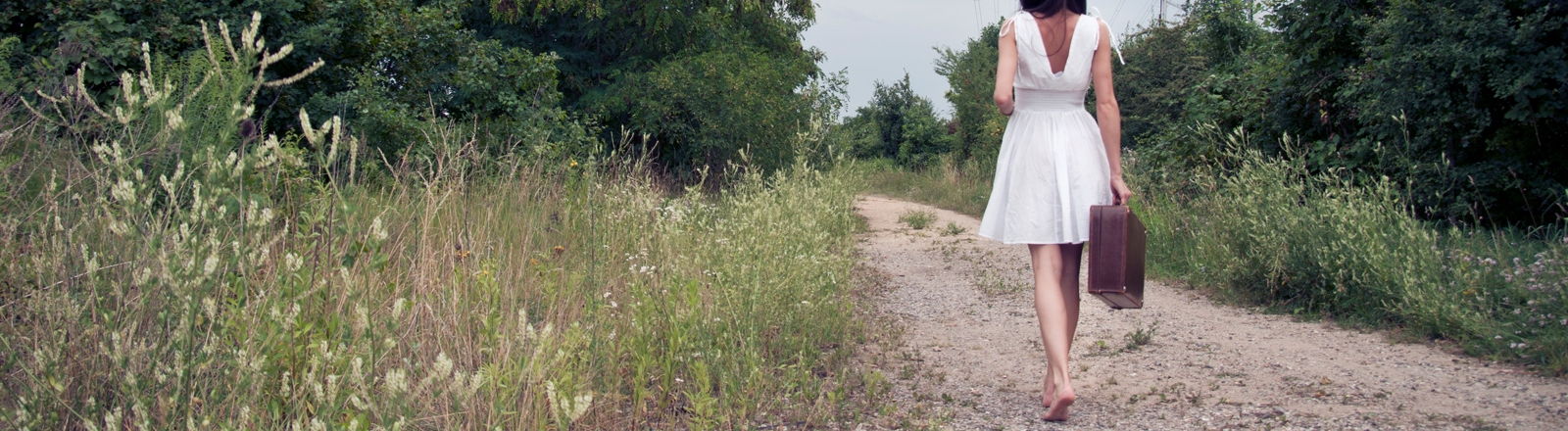 Frau im weißen Sommerkleid irgendwo auf einem Weg.