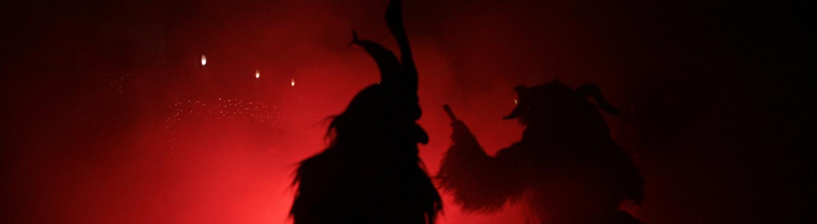 Schatten von Menschen, die sich als Teufel verkleidet haben.