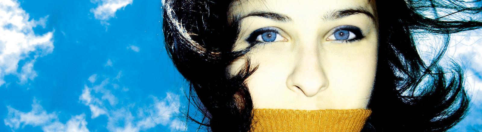 Eine Frau guckt von oben in die Kamera, über ihrem Mund ist ein Pullover, hinter ihr ist ein leicht bewölkter blauer Himmel zu sehen.