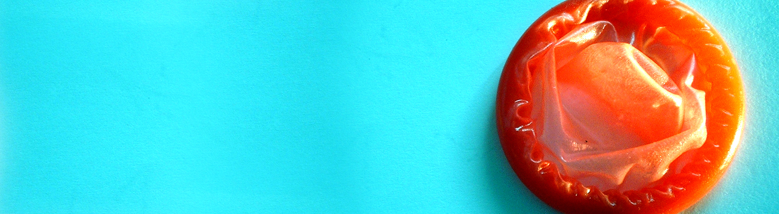 Ein rotes Kondom vor blauem Hintergrund