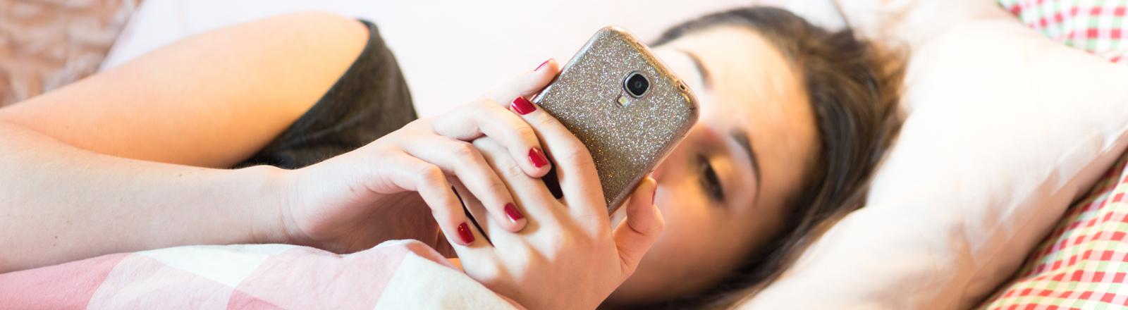Frau liegt mit Smartphone im Bett