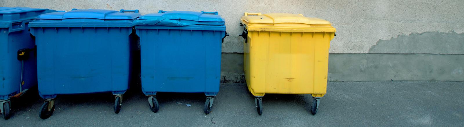 Drei blaue und ein gelber Müllcontainer