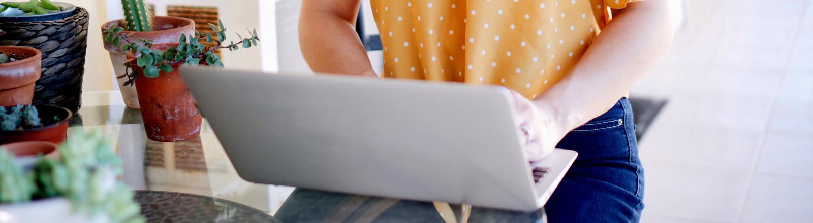 Frau sitzt am Laptop und schreibt.