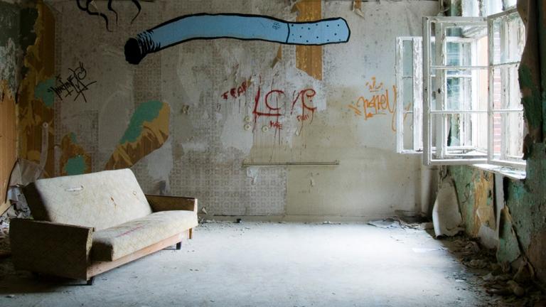 Sofa in einem Zimmer mit ziemlich abgewrackten Wänden.