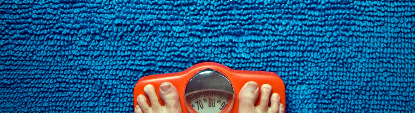 Füße auf einer orangen Waage, die auf einer blauen Badematte steht.