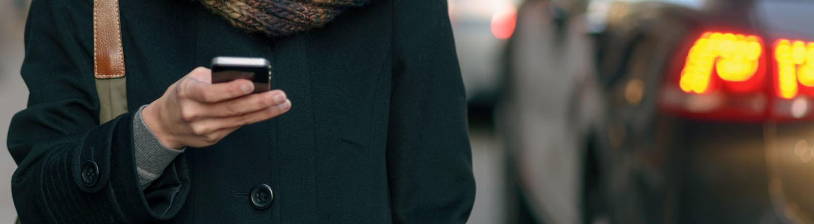 Frau mit Smartphone auf der Straße