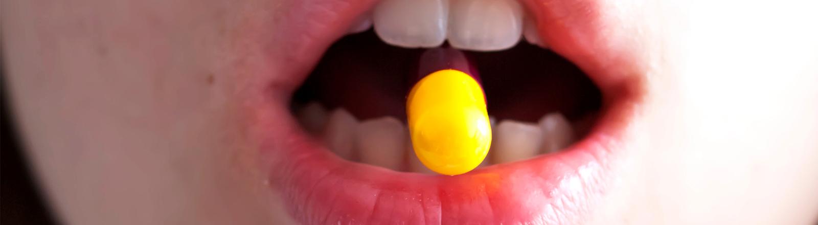 Eine Frau hat eine bunte Pille zwischen den Zähnen
