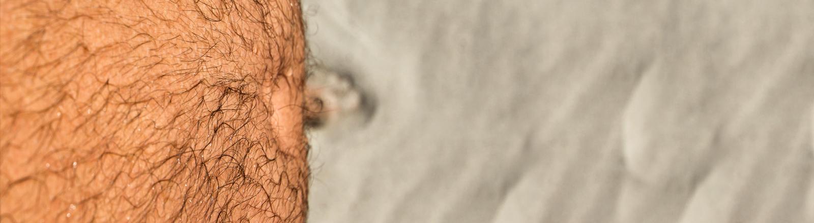 Ein behaarter Männerbauch von oben fotografiert. Im Sand sieht man kaum die Fußspitzen