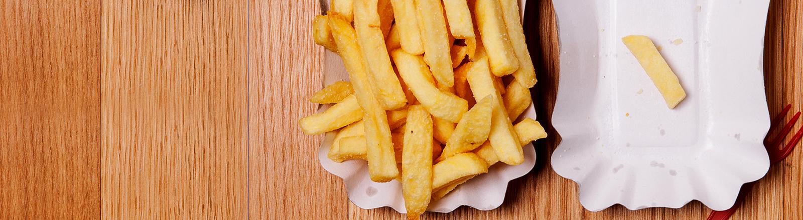 Zwei Schälchen mit Pommes Frittes - eins ist voll, in dem anderen liegt nur eine einzige Fritte.