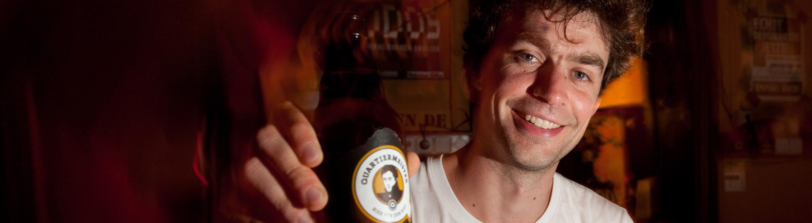 Ein Mann in einer Kneipe hält ein Bier lächelnd in die Kamera