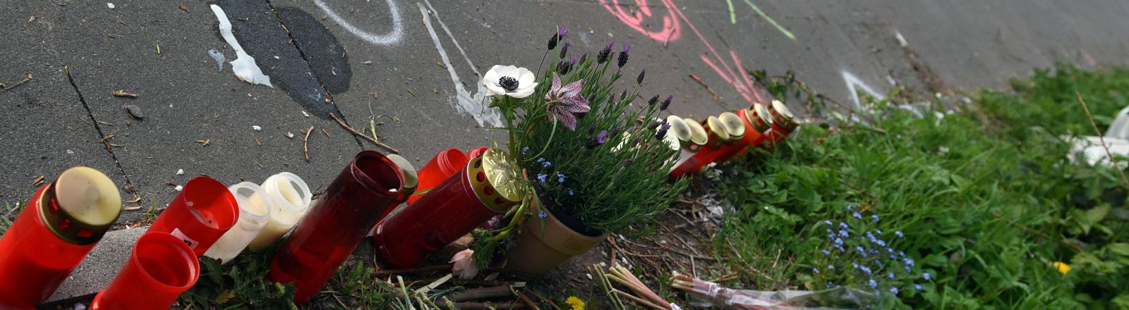 Blumen liegen an der Stelle, an der in Köln eine 19-jährige Radfahrerin durch einen Raser ihr Leben verlor