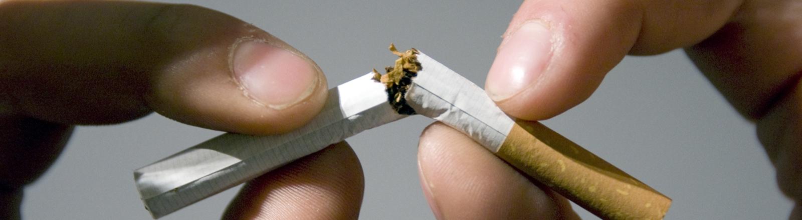 zwei Hände zerbrechen eine Zigarette
