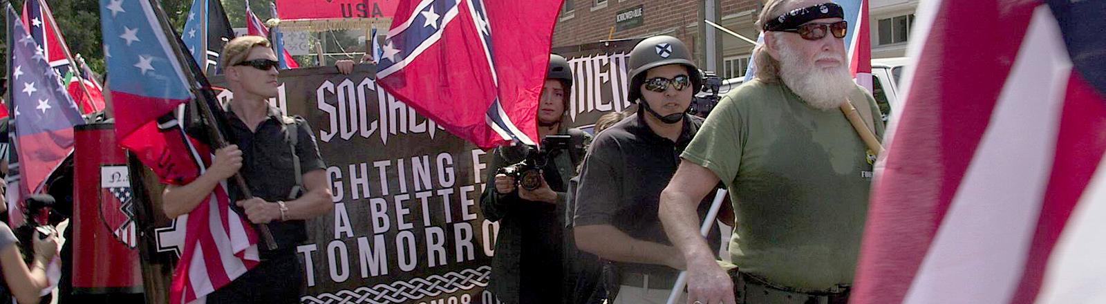 Demonstranten mit USA-Flaggen und rechten Symbolen.