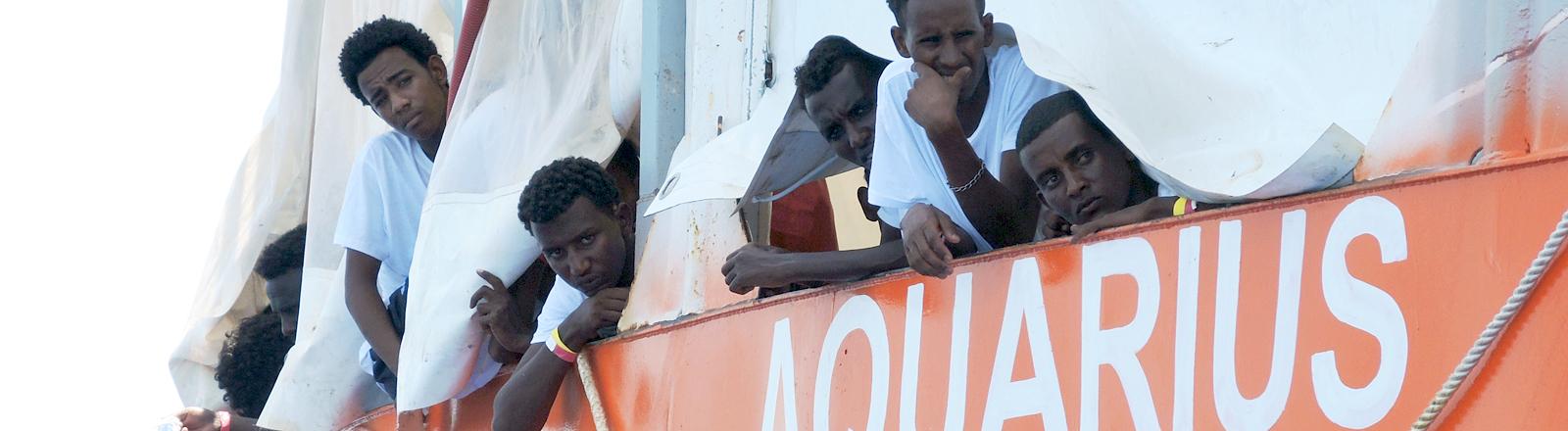 Schwarze Männer schauen aus einem Boot