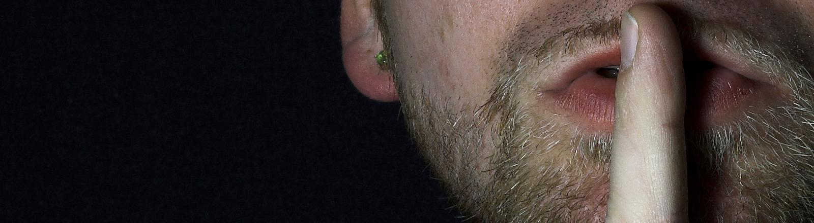 Ein Mann hält sich zum Zeichen still zu sein einen Finger vor den Mund